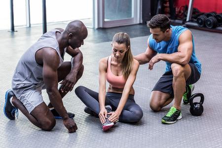 hombre deportista: Mujer muscular que tiene una lesión de tobillo sentado en el suelo