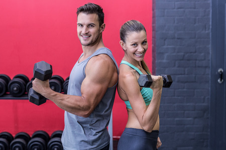 giving back: Muscular couple giving back to back while lifting dumbbells