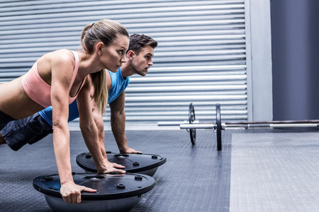 gym room: Side view of a muscular couple doing bosu ball exercises Stock Photo