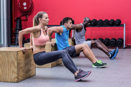 reverse: Muscular athletes doing reverse push up at the crossfit gym Stock Photo