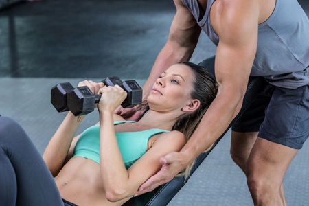 dumbbell: Trainer assisting a muscular woman lifting dumbbells