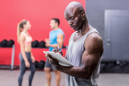 adult  body writing: Side view of a muscular trainer writing on clipboard