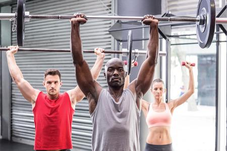 athlete woman: Portrait of three muscular athletes lifting barbells Stock Photo