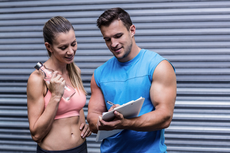 Trainer showing results to a muscular woman on clipboard