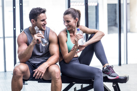 gym room: Muscular couple discussing on the bench and holding water bottle Stock Photo