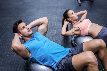 sitting: Muscular couple doing abdominal crunch on a bosu ball