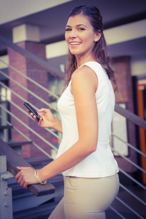 upstairs: Portrait of smiling woman going upstairs while using her smartphone at the shopping mall
