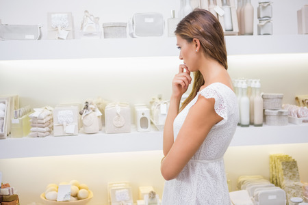 consumer products: Focused woman browsing products at a beauty salon