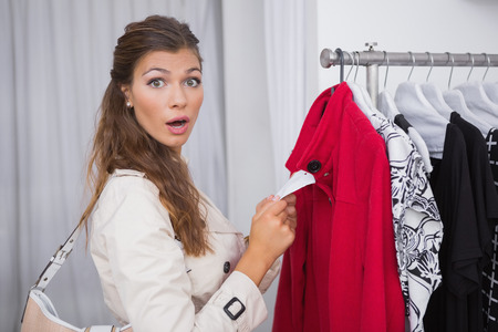 surprised: Retrato de la mujer sorprendida celebración de precio y mirando a la cámara en una boutique