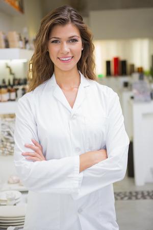 Ritratto di sorridere estetista con le braccia incrociate in un salone di bellezza