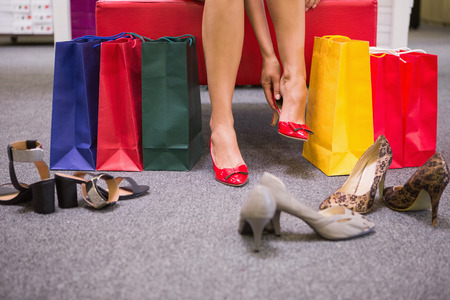 shoe shop: Woman sitting next to shopping bags and putting on shoes at a shoe shop