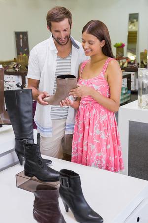 tienda de zapatos: Feliz pareja sonriendo a un zapato en una tienda de zapatos Foto de archivo