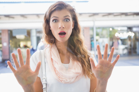 astonishment: Portrait of astonished woman touching window with both hands at the shopping mall