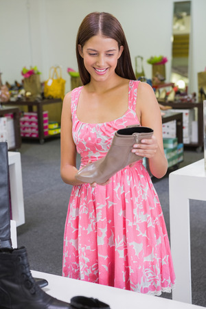 shoe store: Young happy woman looking at a shoe in a shoe store Stock Photo