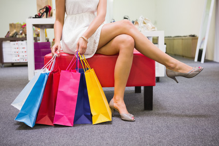 legs crossed: Woman sitting with legs crossed and holding shopping bags at a shoe shop