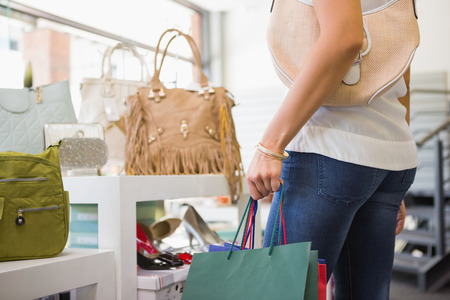 fashion store: Woman browsing bags at a fashion store