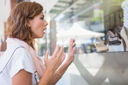 asombro: Mujer asombrosa ventana con una mano tocando en el centro comercial Foto de archivo