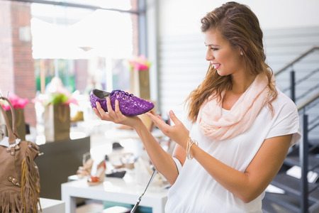 shoe shop: Smiling woman holding laced shoe at a shoe shop Stock Photo