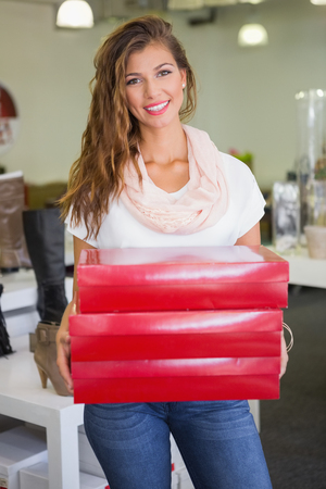 shoe shop: Portrait of smiling woman carrying red boxes at a shoe shop Stock Photo