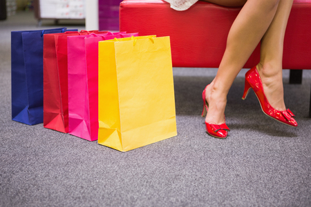 legs crossed: Woman sitting with legs crossed next to shopping bags at a shoe store