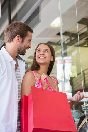long weekend: Happy couple smiling at each other in front of a clothing shop Stock Photo