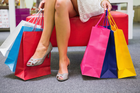 shoe shop: Woman sitting and holding shopping bags at a shoe shop Stock Photo