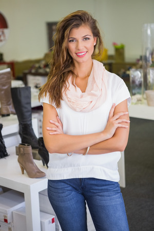 shoe shop: Portrait of smiling woman looking at camera with arms crossed at a shoe shop Stock Photo