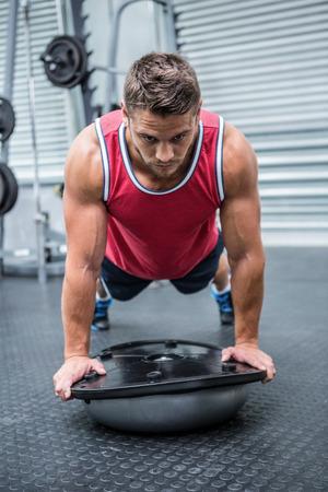 crossfit: Muscular man using bosu ball in crossfit gym Stock Photo