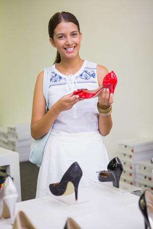 shoe store: Mujer sonriente joven que mira a la cámara con un zapato en la mano en la tienda de zapatos