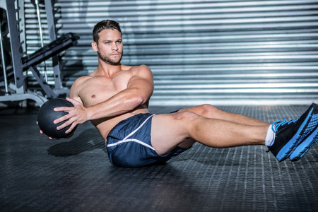 medicina: Hombre muscular que hace ejercicio con bal�n medicinal en el gimnasio de crossfit