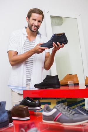 shoe store: Hombre sonriente feliz joven que mira a la cámara mientras sostiene un zapato en la tienda de zapatos