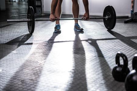 muscular: Hombre musculoso levantar una barra en el gimnasio de crossfit