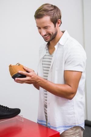 tienda zapatos: Hombre feliz joven sonriendo y mirando a un zapato en la tienda de zapatos