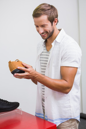 shoe store: Young happy man smiling and looking at a shoe in the shoe store