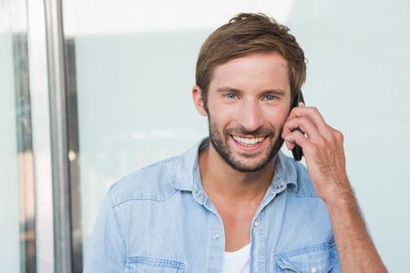 telephoning: Happy man smiling at the camera while telephoning Stock Photo