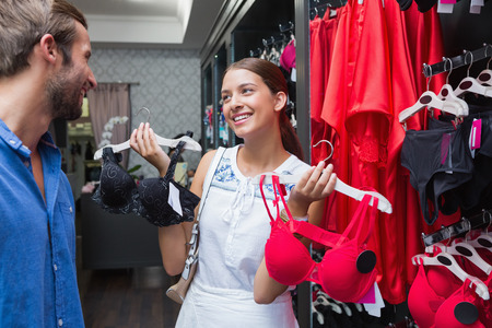 young man short hair: Young happy woman showing clothes to her husband in the clothes store Stock Photo