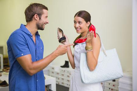 shoe store: Joven pareja de decidir qué zapato para elegir en la tienda de zapatos