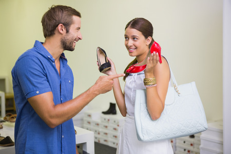 shoe store: Young couple deciding on which shoe to choose in the shoe store Stock Photo