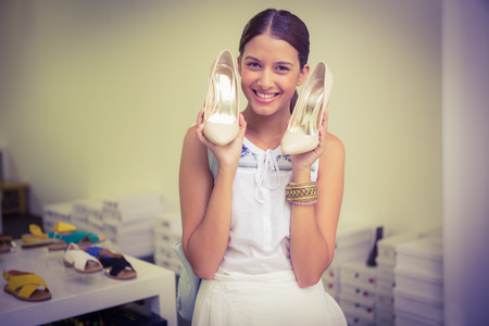 shoe store: Young happy woman holding a pair of shoes in her hand while looking at t he camera in the shoe store