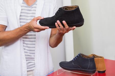 tienda zapatos: Hombre joven que sostiene un zapato en la tienda de zapatos Foto de archivo