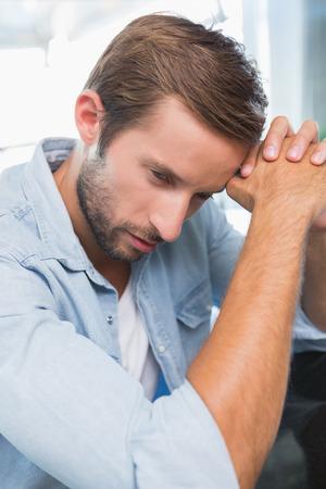 un homme triste: Upset jeune homme dans le caf� Banque d'images