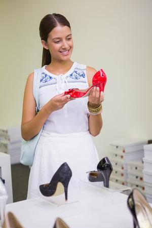 tienda zapatos: Mujer sonriente joven mirando un zapato en la tienda de zapatos