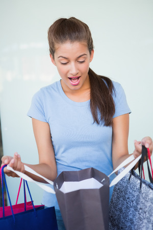 after shopping: Young surprised woman looking at her shopping bags after shopping Stock Photo