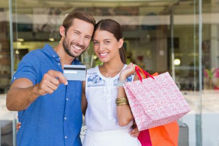 глядя на камеру: Молодая пара счастлива, глядя камеру после покупки, проведение кредитной карты Фото со стока