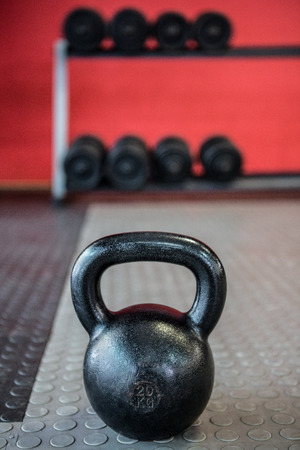 gritty: Close up view of kettlebell in front of dumbbells in crossfit gym