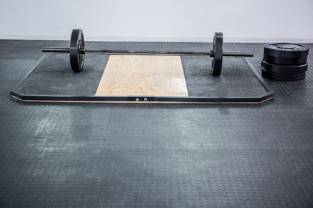 barbell: A barbell next to weights in crossfit gym