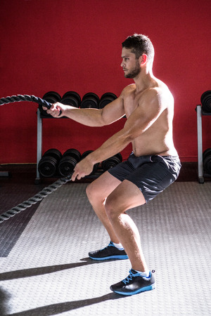 crossfit: Muscular man exercising with rope in crossfit gym