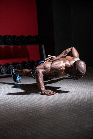 push ups: Young Bodybuilder doing One-armed push ups in front of the camera Stock Photo