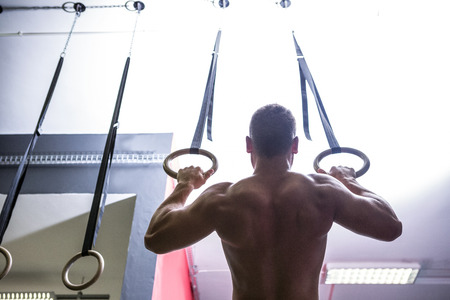 crossfit: Back view of muscular man doing ring gymnastics in crossfit gym