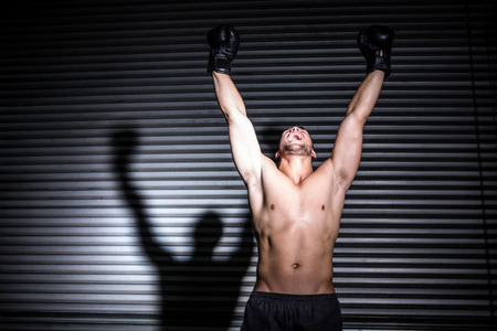 punching: Muscular man punching in the air in crossfit gym Stock Photo